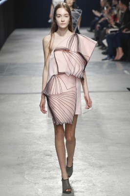 runway fashion photo of a woman in a complex pink dress