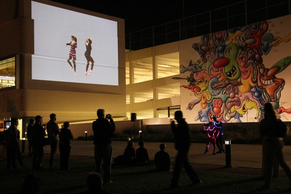 Installation view of a plaza with dancers and projections.
