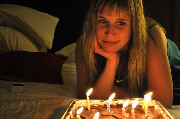 photo of Katrina Schaag with her chin propped on her palm and overlooking a cake with candles burning. The photo has a orange glow from the candlelight which casts half of Katrina Schaag's face in a warm glow and half in shadow