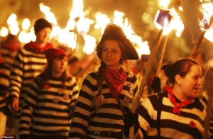 photo of people in striped shirts and pirate hats walking with torches in the night